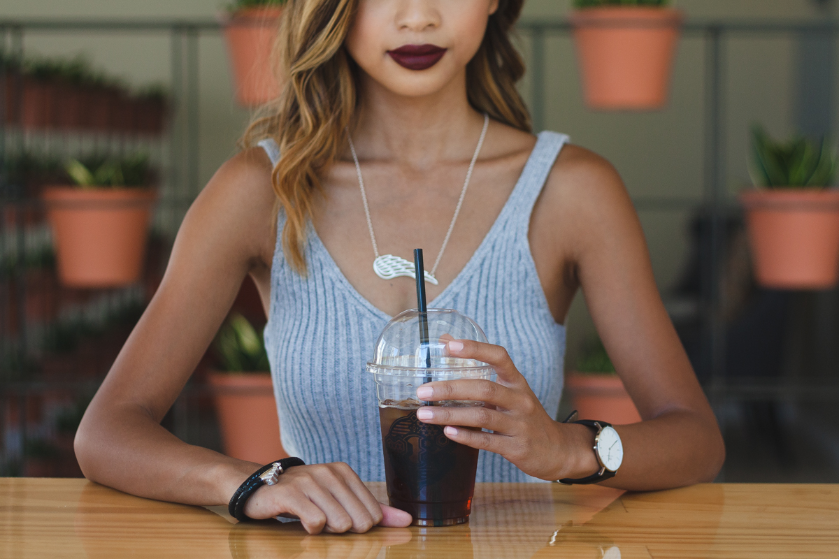 Aiko Cunanan wearing a grey knit dress while sipping coffee